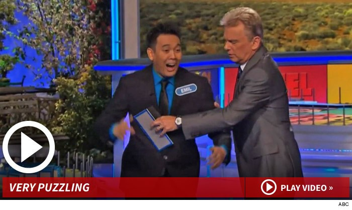 Screen grab of Emil De Leon with host Pat Sajak, jokingly frisking the excited contestant.