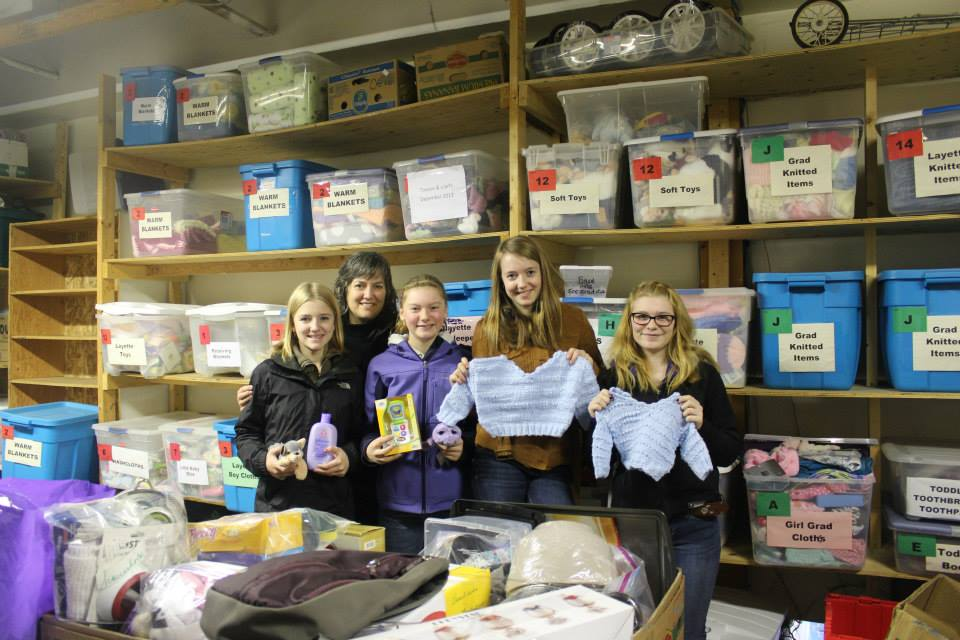 Susan Mercer (second from left) and the young volunteers working in the Tiny Bundles Room of the Surrey Food Bank.