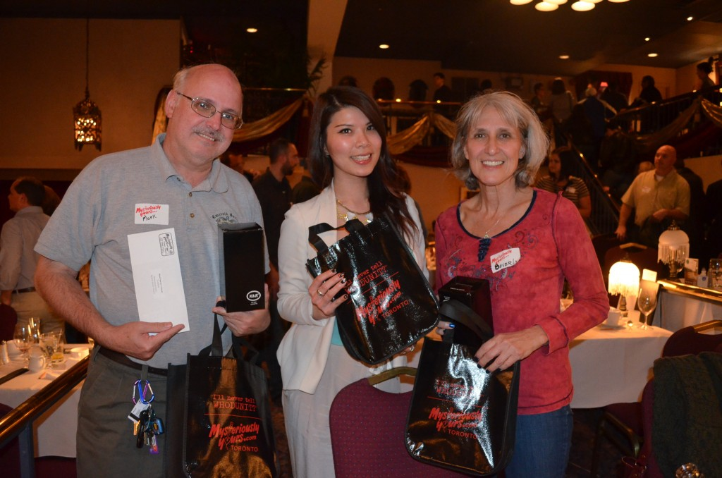 Guests who have guessed whodunit receive their prizes (L-R: Mark Cavanagh, Vanessa Hung, Beverly Cavanagh)