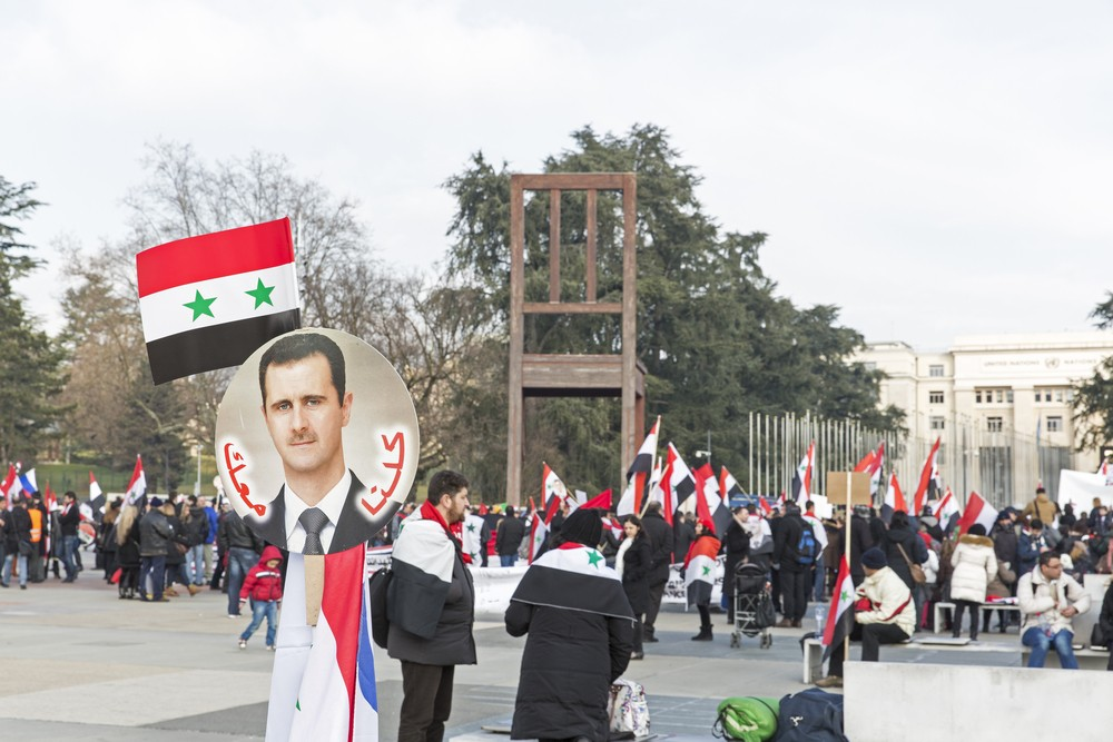Unidentified demonstrators support President Bashar al -Assad of Syria outside the Geneva headquarters of the UN, January 31, 2014, Geneva, Switzerland. FILE PHOTO Martin Good / Shutterstock