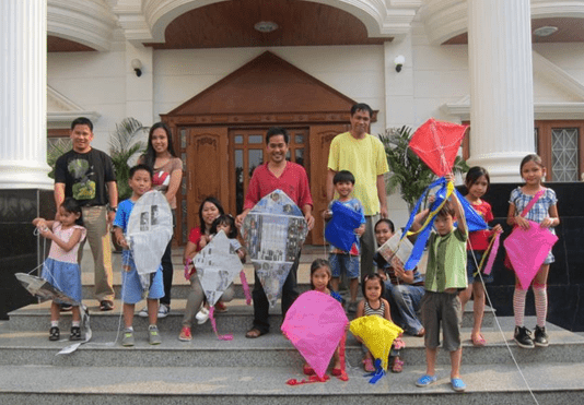 Mr. Giovanni S. Villafuerte (center)  with the Filipino community children and their parents and guardians pose for a photo after flying their hand-made kites at the Philippine Embassy  on 15 March 2014.
