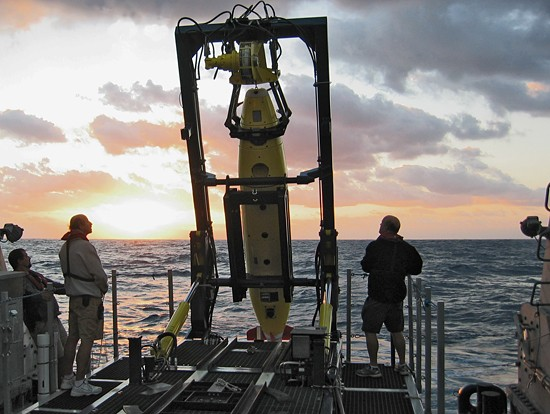 Members of the CATALYST ONE expedition team prepare for a sunrise launch in December 2008 of one of two 6,000-meter autonomous underwater vehicles (AUVs), owned by the Waitt Institute for Discovery. The AUVs were developed at WHOI and were used by scientists at Harbor Branch Oceanographic Institute to create the first-ever high definition side-scan sonar maps of deep-water Lophelia and Oculina coral reefs off the coast of eastern Florida. The expedition was the first in a new partnership between WHOI and the Waitt Institute for Discovery to make available to a wide range of science users a versatile and highly portable deep-sea tool kit and operations team that is rapidly deployable all over the world. (Photo by Mike Purcell, Woods Hole Oceanographic Institution)