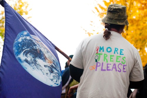 "WASHINGTON, DC-OCT 24:An environmental activist with a shirt saying ""More Trees Please"" flies a flag with the planet earth during the International Day of Climate Action October 24, 2009 in Washington (Photo by Ryan Rodrick Beiler / Shutterstock.com)"