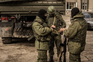 MARCH 5 2014: Russian troops without chevrons and distinctive signs, near of the truck without license plates (March 5, 2014) Sergii Morgunov / Shutterstock