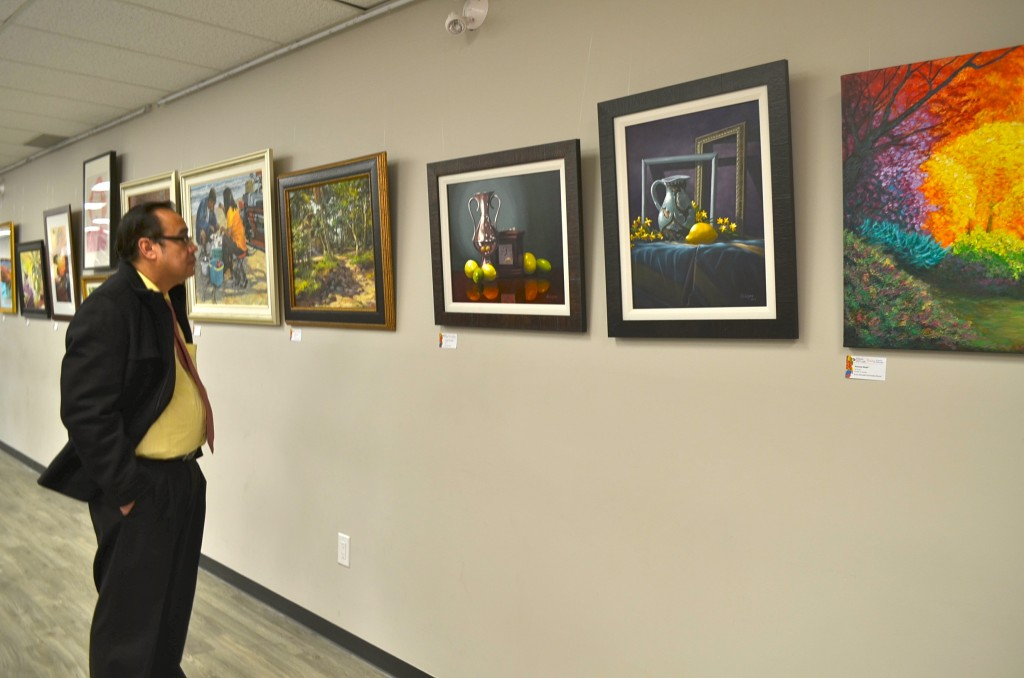 One of the guests viewing paintings by Filipino Artists/ Photos by Thessa Sandoval