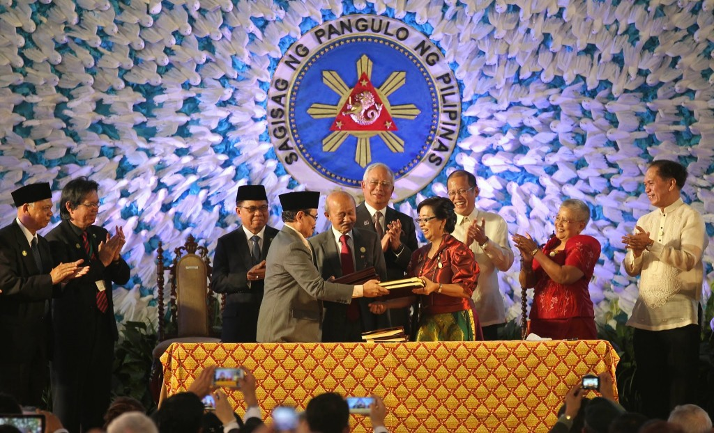 President Benigno S. Aquino III and Malaysian Prime Minister Najib Razak witness MILF Peace Panel chairman Mohagher Iqbal, GPH Peace Panel chairperson Professor Miriam Coronel-Ferrer and Malaysian facilitator Tengku Ghafar affix their signature to the Comprehensive Agreement on the Bangsamoro in a ceremony at the Kalayaan grounds of the Malacañan Palace on Thursday (March 27). Also in photo are MILF chairman Al Haj Murad Ebrahim and Presidential Adviser on the Peace Process Secretary Teresita Quintos-Deles. (Photo by Gil Nartea/ Robert Viñas/ Rodolfo Manabat/ Malacañang Photo Bureau)