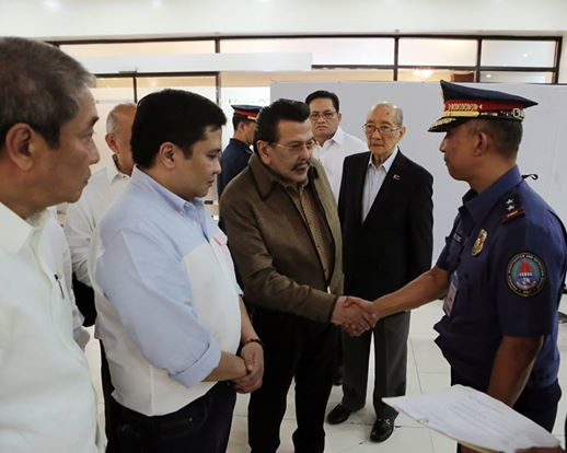 "Manila City Mayor Joseph ""Erap"" Estrada submits his son, Senator Jinggoy Ejercito Estrada to the Philippine National Police through PNP CIDG Director, Police Director Benjamin Magalong before undergoing mandatory booking procedure at Camp Crame, Quezon City after the Sandiganbayan 5th Division issued the Warrant of Arrest against the Senator in connection with a Plunder Case. (PNP-PIO)"