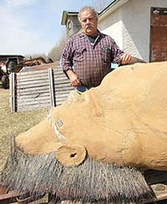 1.Albert Klyne shows off the statue he made of the creature he says he spotted near his home south of Portage la Prairie, Manitoba in 2001. (Photo: Jason Halstead, Sun Media / sasquatchcanada.com ).Tilt your head, to see the proper configuration of the object he carved.