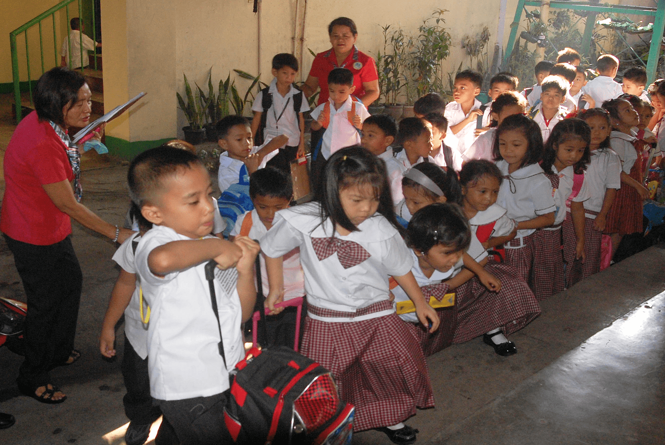 Fulgencia T. Ogot,(left photo) principal of Camarin Elementary School in Caloocan City helps kindergarten pupils in going to their assigned classroom for the opening of classes Monday, June 2, 2014. (PNA photo by Johnny D. Guevarra)