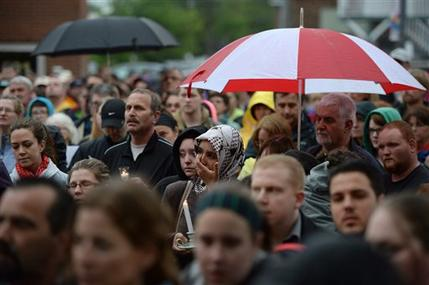 People take part in a candlelight vigil outside Royal Canadian Mounted Police headquarters in Moncton, New Brunswick, Canada on Friday, June 6, 2014. The RCMP say Justin Bourque, suspected in the shooting deaths of three Mounties and the wounding of two others in Moncton, was unarmed at the time of his arrest early Friday and was taken into custody without incident. Sean Kilpatrick / AP Photo / The Canadian Press/