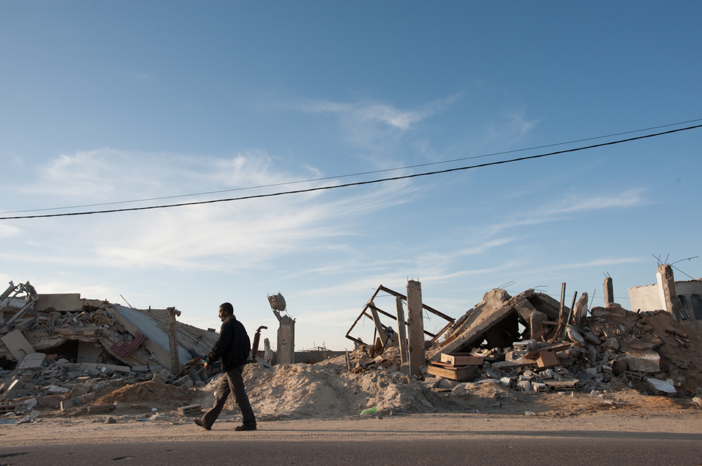 A man walk nears rubble from Israeli bombings that destroyed a medical clinic and other structures in a community near Khan Yunis, Gaza. Ryan Rodrick Beiler / Shutterstock