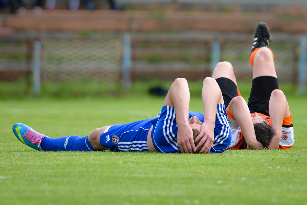 LUBIN, POLAND—JUNE 5, 2014: Michal Bierzalo (L) and Kamil Maternik (R) injured during match 1/4 final Polish Junior Championships betwen KGHM Zaglebie Lubin - Wisla Krakow(0:2). Photo by Dziurek / Shutterstock.com.