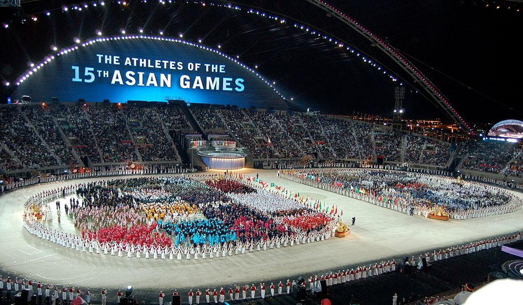 Athletes of the 2006 Asian Games gathered at the center of a main stadium during the opening ceremony. Photo by le dieu / Flickr.
