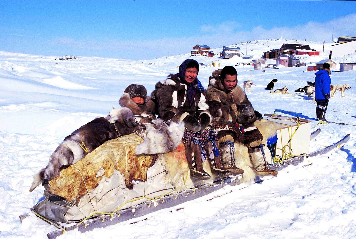 Inuit people on a traditional qamutik (dog sled), Cape Dorset, Canada. Photo by Ansgar Walk / Wikimedia Commons.