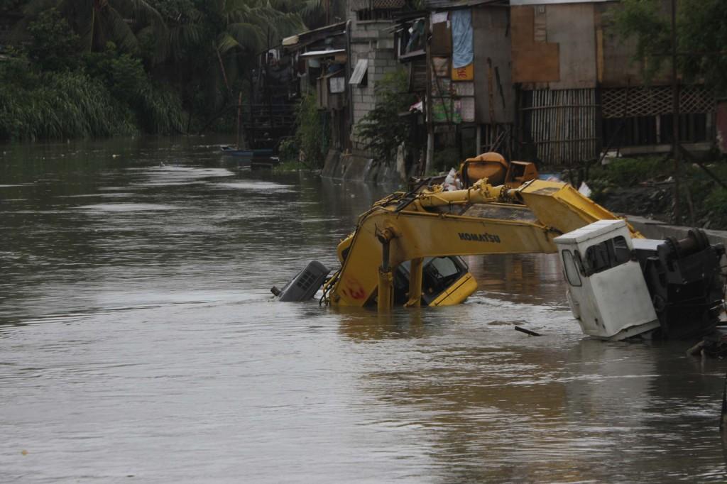 Photo shows a heavy equipment half-submerged in the swollen water of Bacoor River in Bacoor City, Cavite on Friday (Sept. 19, 2014). (PNA photo by Avito C. Dalan)