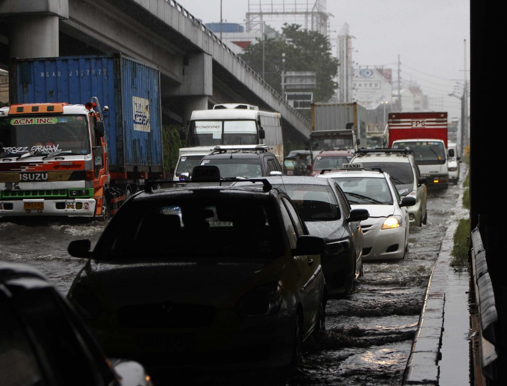 "Vehicles of different types move bumper-to-bumper along Osmena Highway in Makati City due to floodwater caused by heavy rains spawned by tropical storm ""Mario"" on Friday (Sept. 19, 2014). (PNA photo by Avito C. Dalan)"