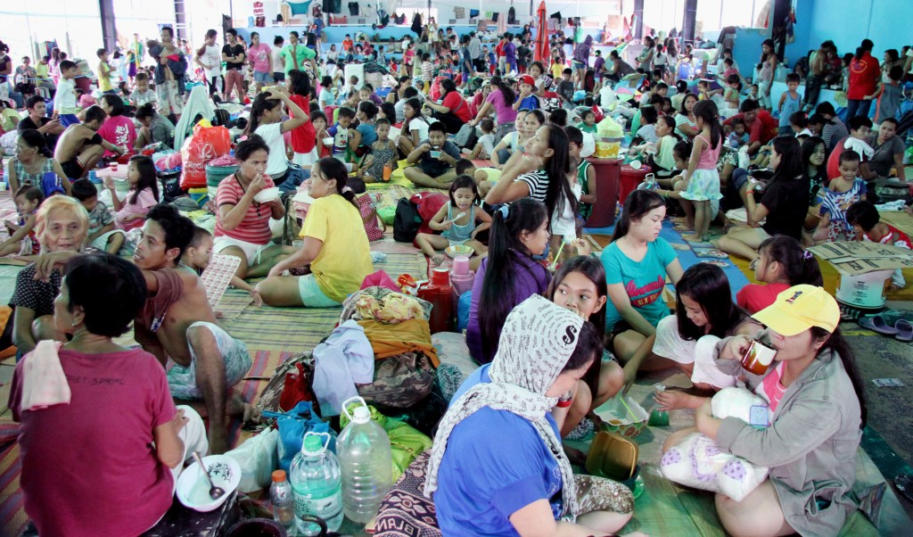 Volunteers assist more than 5,000 evacuees who are still housed at a covered court in Barangay Silangan, Quezon City. As of 9:15 a.m. Saturday, records show that at least 5,688 residents remain in said evacuation center. Thousands of other residents are said to have returned to their homes as the weather improves. (PNA photo by Oliver Marquez)
