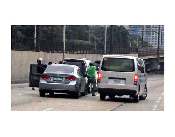 This hurriedly taken eyewitness photo shows armed men surrounding a vehicle along EDSA mid-afternoon of Monday, Sept, 1.
