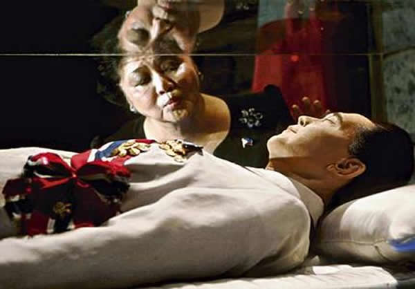Imelda Marcos kisses the encasement of her late husband's body.  (Photo from www.scrapetv.com)