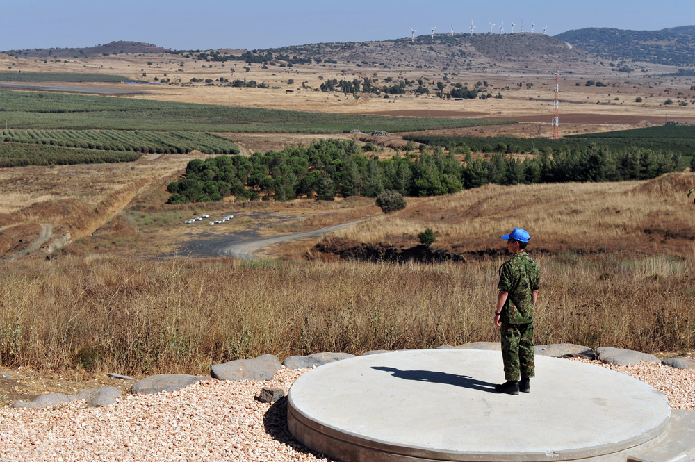 An UNDOF soldier examines the Israeli-Syrian border in Golan Heights, Israel. It was established in 1974 by the Security Council resolution 350 following the Yom Kippur war. Photo by ChameleonsEye / Shutterstock.com.