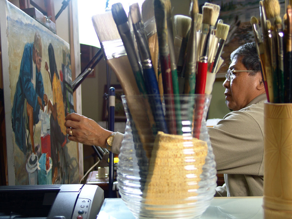 The Maestro, Romi Mananquil, working on a painting in his basement studio.