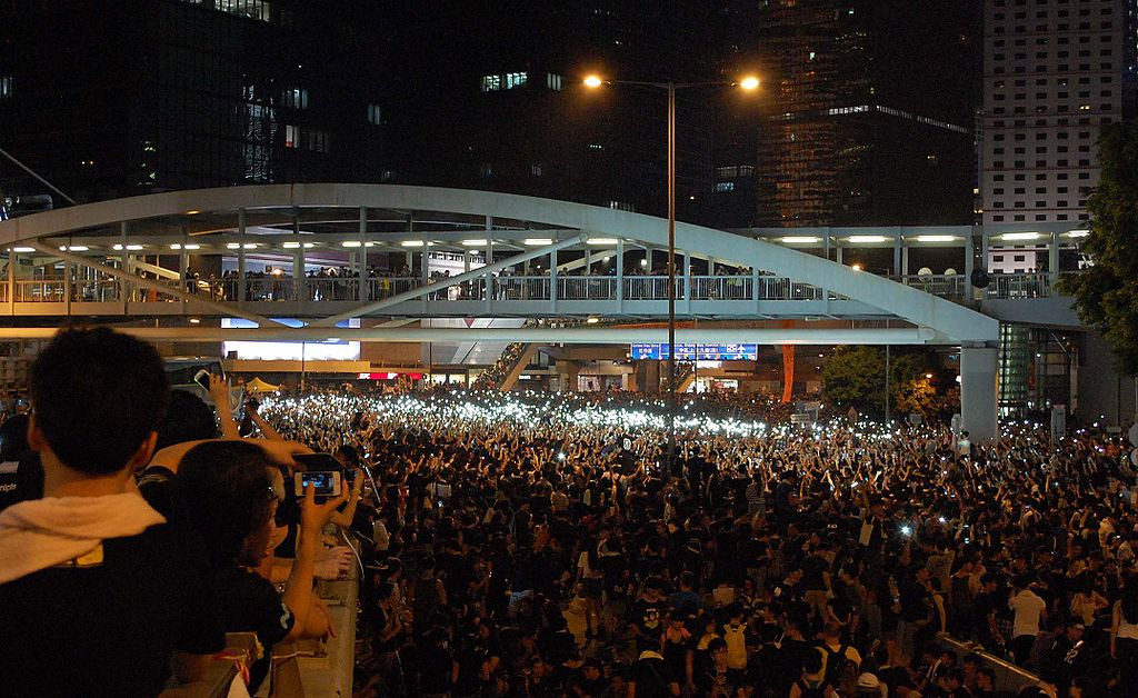 "Protesters occupying Harcourt Road, Admiralty hold a ""candlelight vigil"" (with mobile phones) during Occupy Central, 2014 Hong Kong protests. Citobun / Wikimedia Commons."