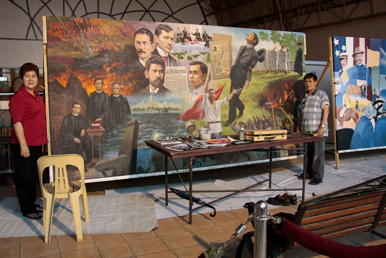 Romi stands by his mural with wife Necie at the U.P. Bahay ng Alumni lobby.