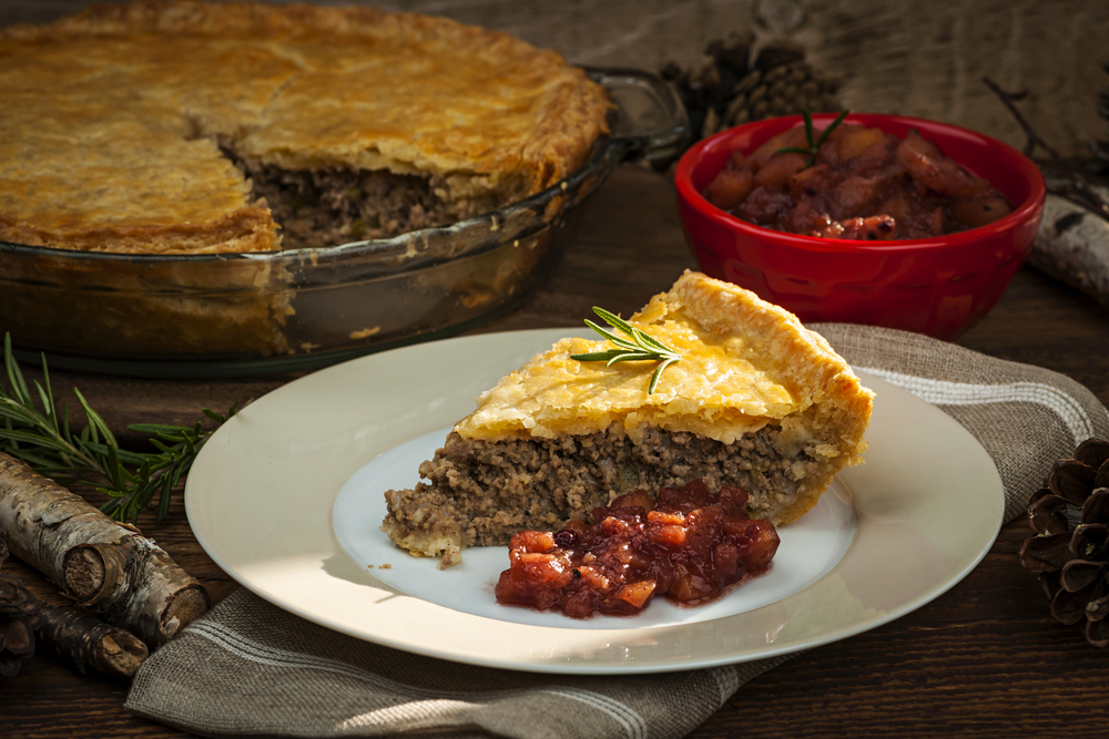 Slice of traditional pork meat pie Tourtiere with apple and cranberry chutney from Quebec, Canada. (ShutterStock image)