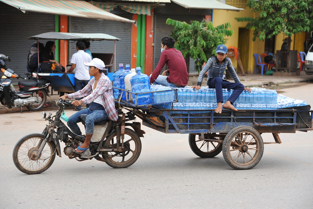 Workers transport water by motorcycle and cart in Siem Reap, Cambodia. Despite Cambodia's growing economy 20% of the population live below the poverty line. 1000 Words / Shutterstock.com