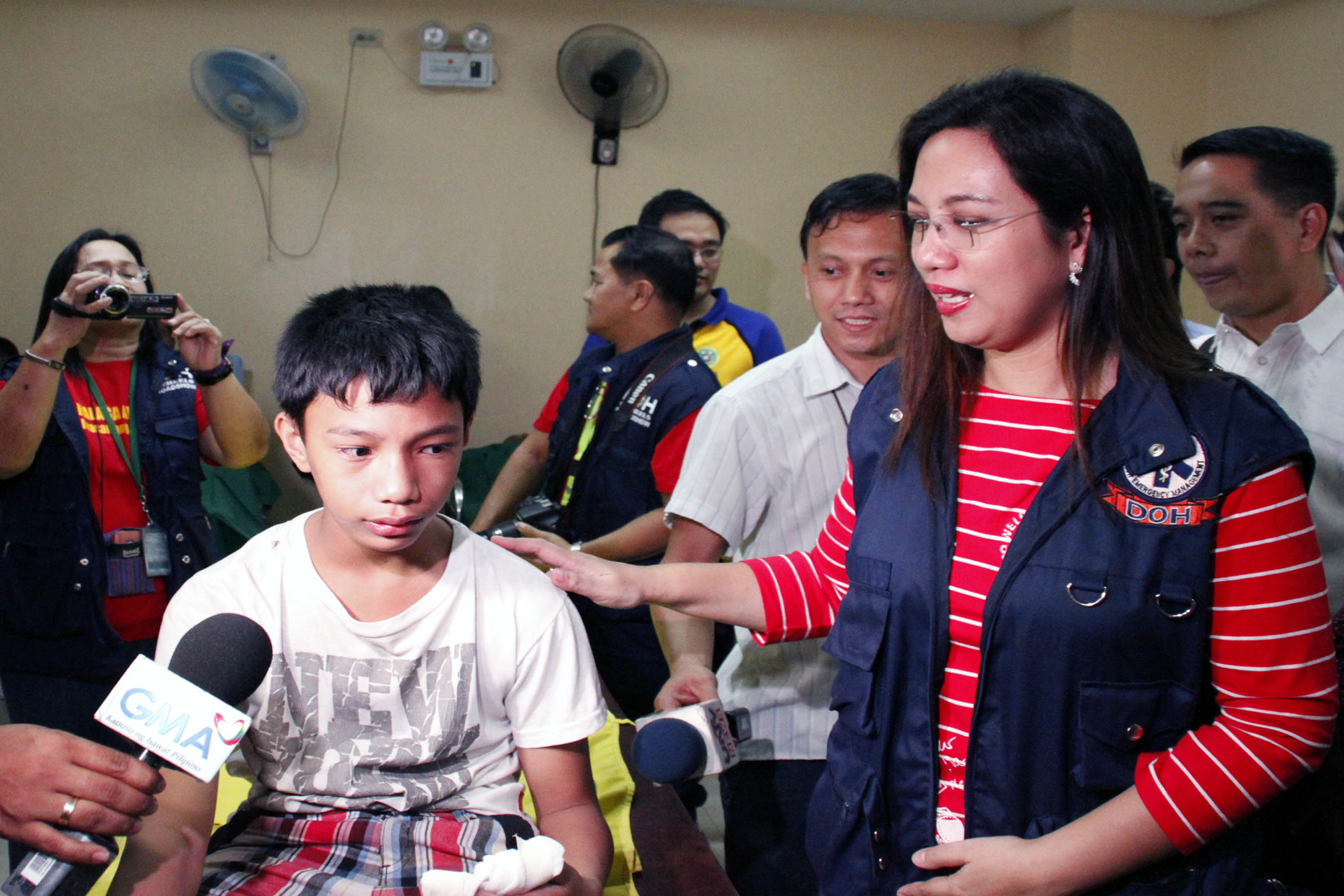 Department of Health (DOH) Acting Secretary Janette L. Garin comforts 13-year-old Justin Garcia who is confined at the Philippine Orthopedic Center (POC) in Quezon City after he was injured in a piccolo firecracker explosion. Dr. Garin visited the POC on New Year's Eve Wednesday (Dec. 31, 2014). (PNA photo by Joey O. Razon)