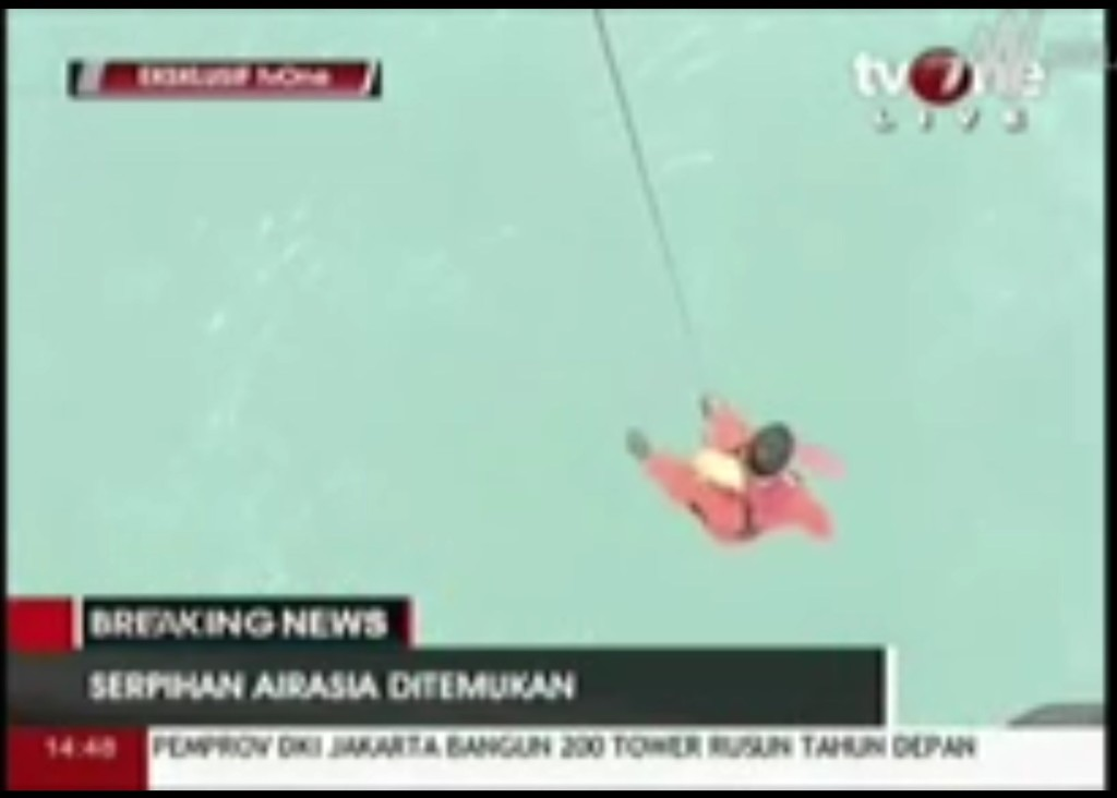 An Indonesian rescuer is lowered into the water to retrieve an unideitified floating body, presumably from the AirAsia plane wreckage. (screenshot from AP footage)