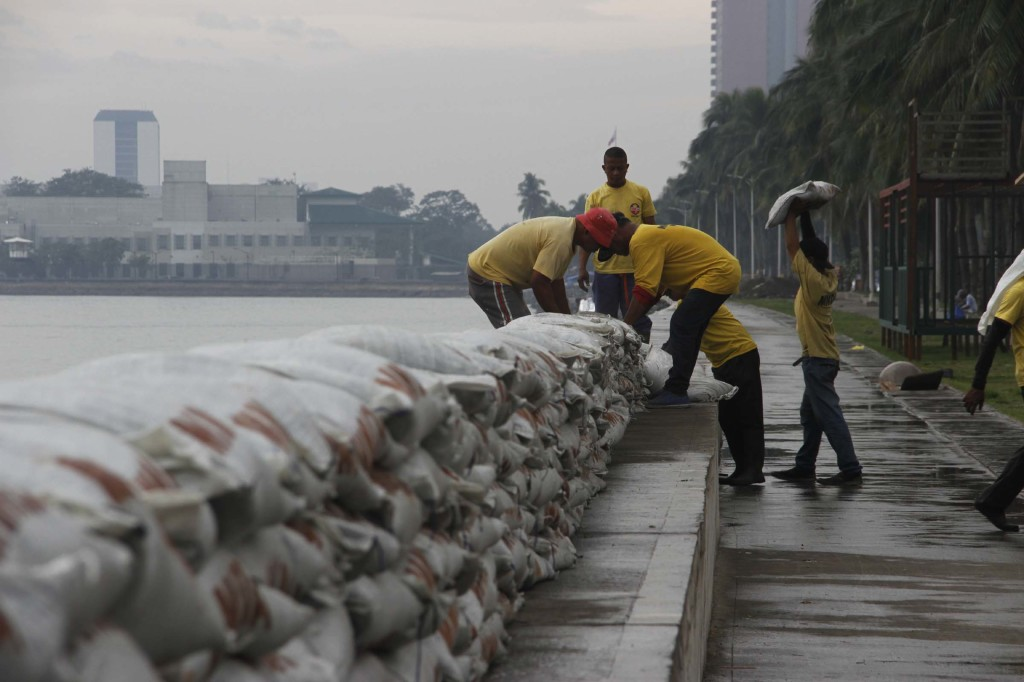 """Metropolitan Manila Development Authority (MMDA) personnel put sandbags along a portion of the Roxas Blvd. Baywalk in Manila as part of the precaution against possible storm surges that maybe caused by Tropical Storm """"Ruby"""" which is expected to pass south of Metro Manila on Monday evening (Dec. 8, 2014). (PNA photo by Avito C. Dalan)"""
