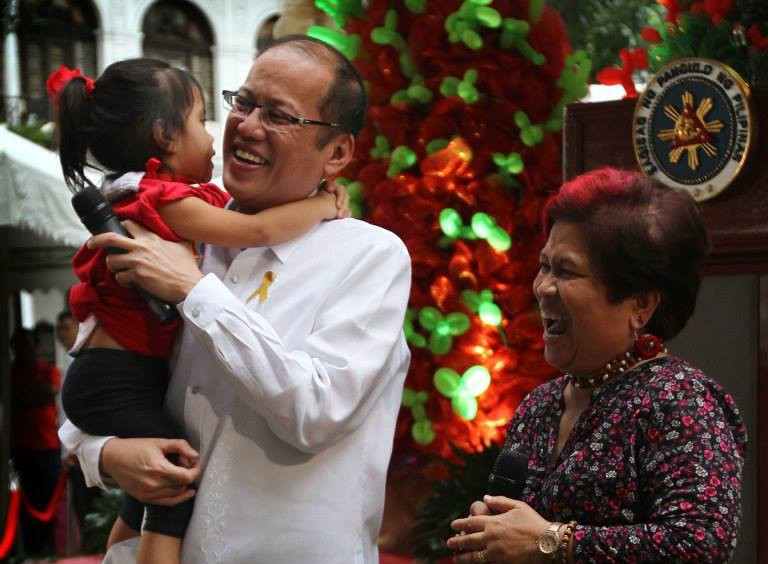 President Benigno S. Aquino III carries a child during the Pasko ng Batang Pinoy 2014 at the Kalayaan Grounds of the Malacañan Palace on Friday (December 19, 2014). The Pasko ng Batang Pinoy Project is part of The DSWD's program to provide the street children a venue for self-enhancement through various activities to enjoy the spirit of Christmas while impede them from going out the streets especially this yuletide season. Also in photo is Social Welfare and Development Secretary Corazon Juliano-Soliman. (Photo by Exequiel Supera / Malacañang Photo Bureau / PCOO)