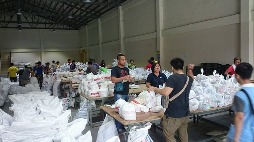 Members of the Philippine Air Force assist in the repacking of relief goods at the DSWD NROC. (Photo via the Philippine Air Force)