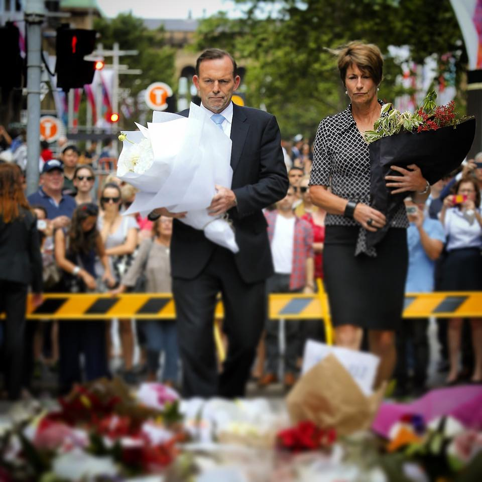 Australian Prime Minister Tony Abbott and wife Margie Aitken-Abbott lay down flowers the day after the Martin Place siege that claimed three lives. (Facebook photo)