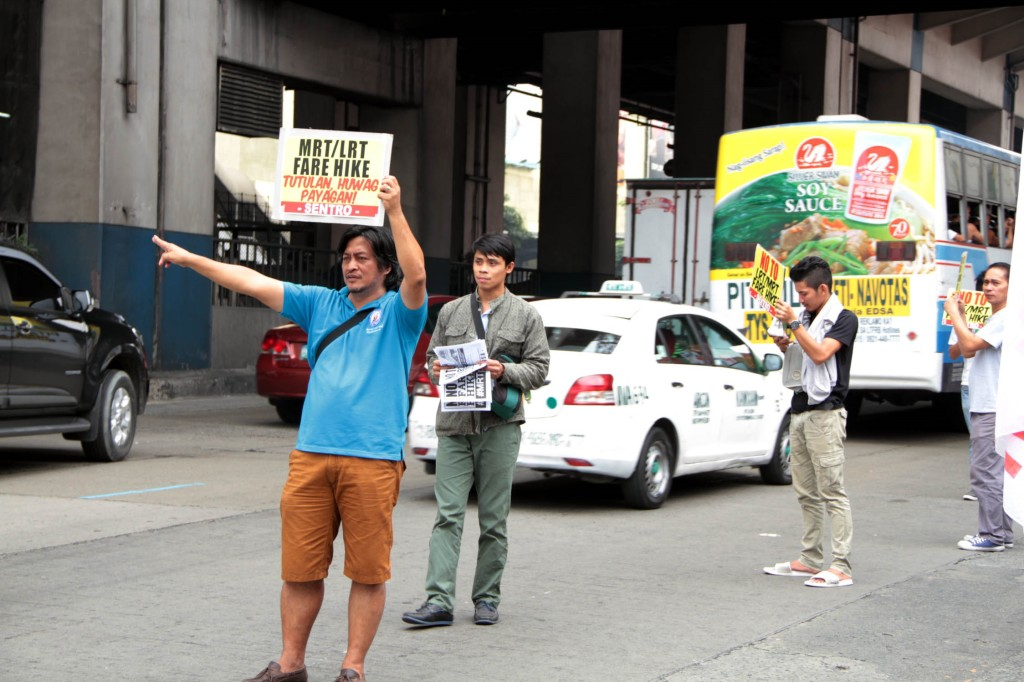 Workers hold a rally in front of the Metro Rail Transit (MRT) 3 North Avenue Station in Quezon City on Monday (Jan. 5, 2015) to express opposition to fare increases of the MRT and Light Rail Transit (LRT) Lines 1 and 2. (PNA photo by Jess M. Escaros Jr.)