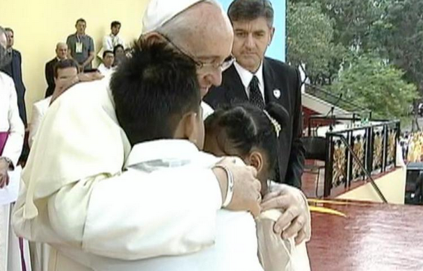 Pope Francis hugs and comforts two former street children during the 'Encounter with the Youth' event at the Royal and Pontifical University of Santo Tomas, January 18, Sunday. (Photo courtesy of Radio-Television Malacanang)