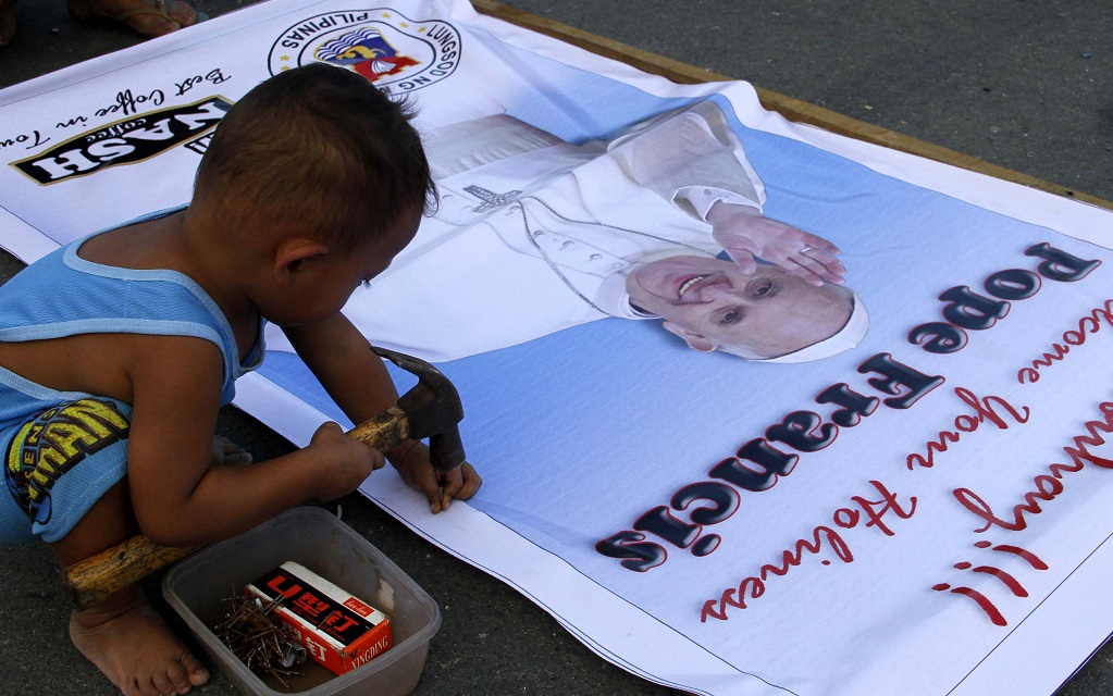 3-year-old Paulo Domingo helps his father by trying to fix the nails to the picture frame in preparation for Pope Francis visit on January 15-19 at the Quirino Grandstand, Manila on Saturday (January 3, 2015). (PNA photo by Avito C. Dalan)