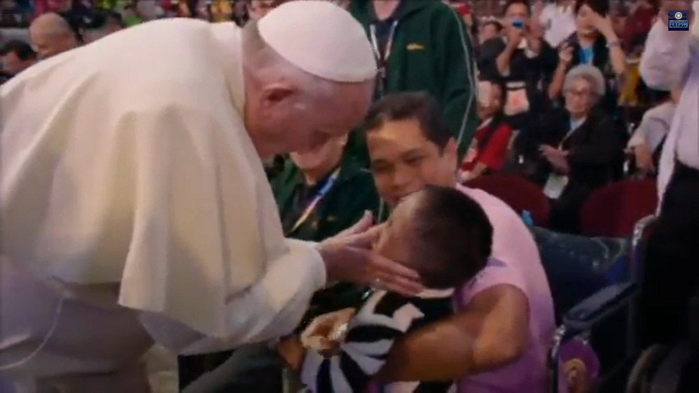 Pope Francis touches and blesses a sick child a the Mall of Asia Arena.