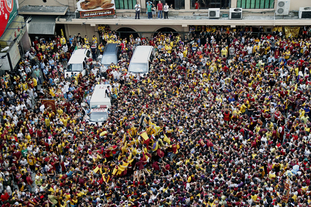 Hundreds of thousands devotees line up the streets of Manila to await the Procession of the Black Nazarene on Friday (Jan. 9, 2015). Photo shows the crowd along Escolta St., Binondo, Manila as the Black Nazarene passes on its way back to Quiapo Church. (PNA photo by Oliver Marquez)