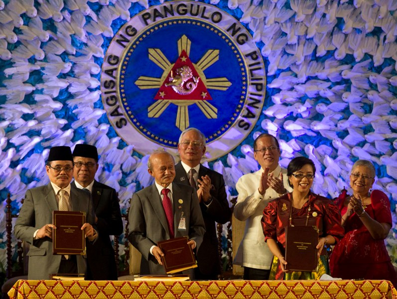 President Benigno S. Aquino III and Malaysian Prime Minister Najib Razak witness MILF Peace Panel chairman Mohagher Iqbal, Malaysian facilitator Tengku Ghafar, Presidential Adviser on the Peace Process Secretary Teresita Quintos-Deles affix their signature to the Comprehensive Agreement on the Bangsamoro in a ceremony at the Kalayaan Grounds of the Malacañan Palace on Thursday (March 27). Also in photo are MILF chairman Al Haj Murad Ebrahim,Presidential Adviser on the Peace Process Secretary Teresita Quintos-Deles,MILF Peace Panel chairman Mohagher Iqbal,GPH Peace Panel chairperson Professor Miriam Coronel-Ferrer and Malaysian facilitator Tengku Dato Abdul Ghafar (Photo by Ryan Lim/ Malacañang Photo Bureau)