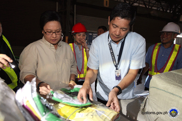 Customs Deputy Commissioner for Intelligence Jessie Dellosa and Zsae Carrie de Guzman of the Bureau of Customs' Intellectual Property Rights Division (1st and 2nd from right, respectively) inspect counterfeit T-shirts seized from a shipment that arrived from China a few days ago at the Manila International Container Port. (boc.gov.ph)