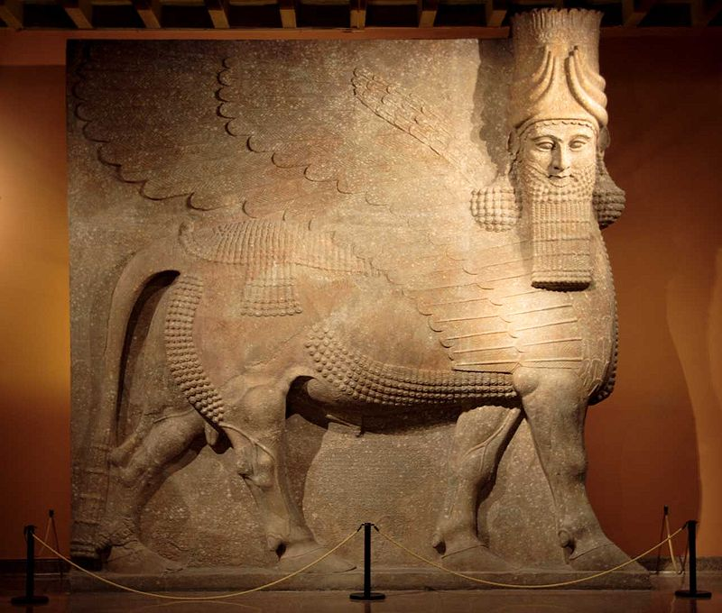 This is the Assyrian Lamassu at the Oriental Institute Museum at the University of Chicago. Gypsum (?) Khorsabad, entrance to the throne room Neo-Assyrian Period, ca. 721-705 B.C. OIM A7369 This 40 ton statue was one of a two flanking the entrance to the throne room of King Sargon II. A protective spirit known as a lamassu, it is shown as a composite being with he head of a human, the body and ears of a bull, and the wings of a bird. When viewed from the side, the creature appears to be walking; when viewed from the front, to be standing still. Thus it is actually represented with five, rather than four legs.  (Wikipedia)