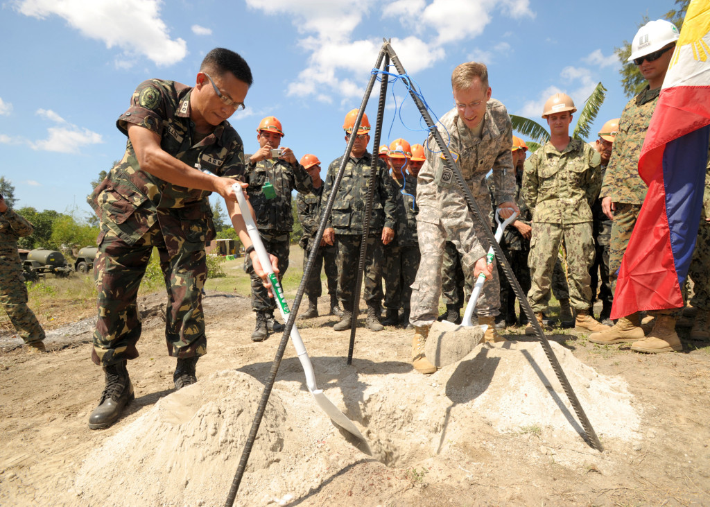 Philippine army Lt. Col. Henry Bellan, left, and U.S. Army Lt. Col. John Garrity, the deputy commanders of Joint Civil Military Operations Task Force, bury a time capsule containing the construction plans for a footbridge during a groundbreaking ceremony March 18, 2013, in San Narciso, Philippines. The job was one of eight engineering civic action projects conducted by U.S. and Philippine service members in support of exercise Balikatan 2013. Balikatan is an annual bilateral training exercise designed to increase interoperability between the Armed Forces of the Philippines and the U.S. military when responding to future natural disasters. (DoD photo by Mass Communication Specialist 1st Class Chris Fahey, U.S. Navy/Released -- Wikipedia photo)