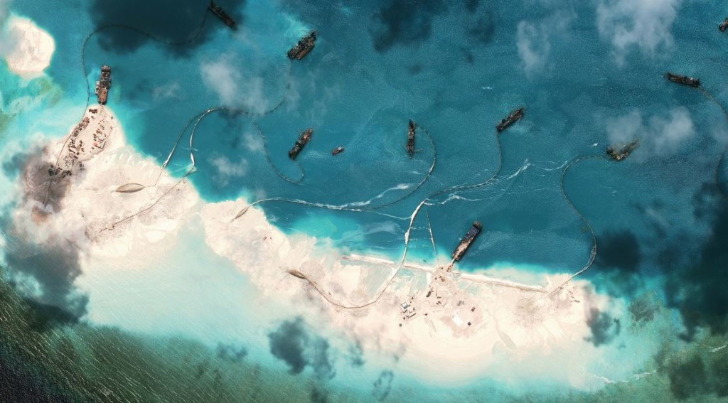 This handout photo taken on March 17, 2015 by satellite imagery provider DigitalGlobe and released to AFP by the Asia Maritime Transparency Initiative department at the Center for Strategic and International Studies (CSSI) think tank shows a satellite image of vessels purportedly dredging sand at Mischief Reef in the Spratly Islands in the disputed South China Sea.  The series of satellite images posted on the website of the Center for Strategic and International Studies last week show a flotilla of Chinese vessels dredging sand onto Mischief Reef and the resulting land spreading in size. Beijing on April 9 reaffirmed its right to build on the disputed islands after the satellite imagery emerged of construction operations turning tropical reefs into concrete artificial islands. The Philippines, Vietnam, Malaysia, Brunei and Taiwan all have overlapping claims in the area. (AFP Photo / CSIS Asia Maritime Transparency Initiative / DigitalGlobe)