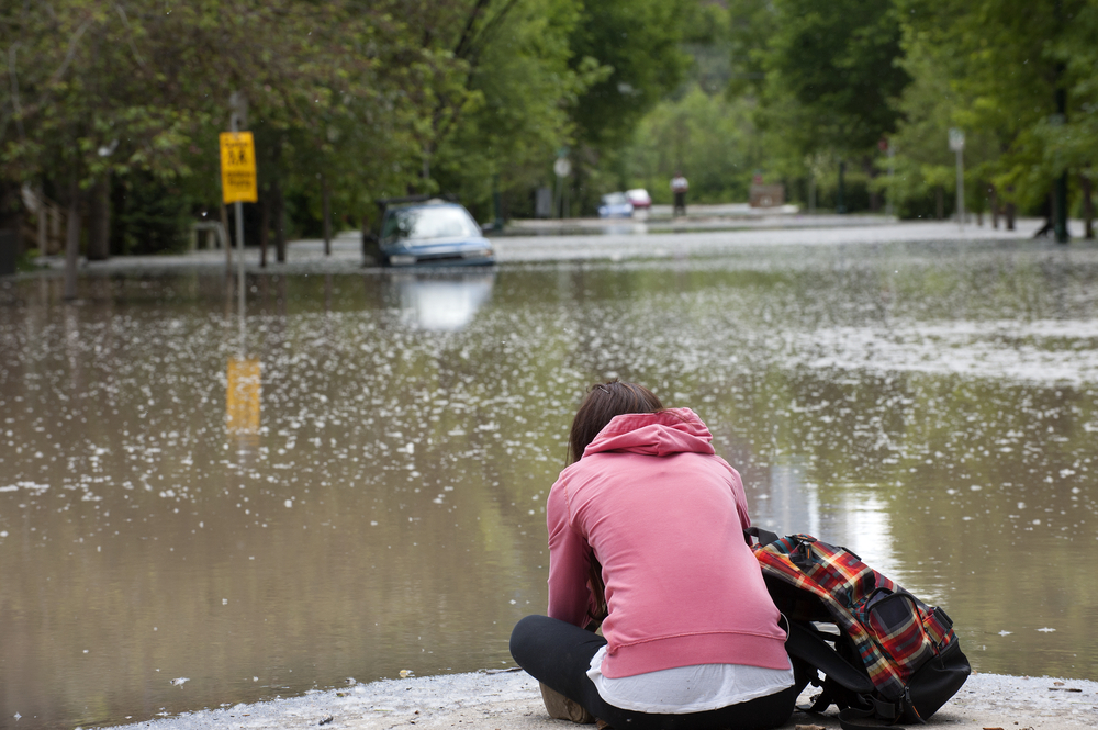 Woman looks at flooded street during the 2013 Calgary flooding (shutterstoc)