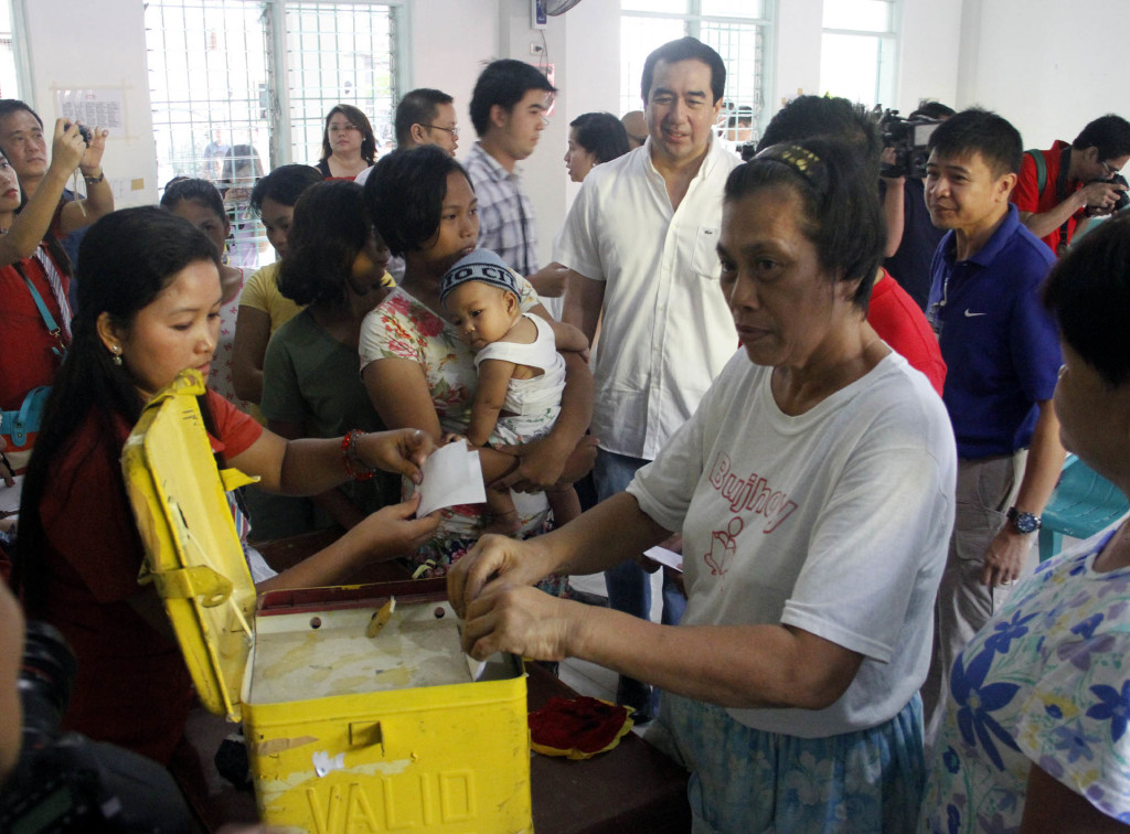 A woman casts her votes as Comelec Chairman Andres Bautista looks on during mock elections held at Bacoor National High School in Bacoor, Cavite. (PNA photo by Avito Dalan)