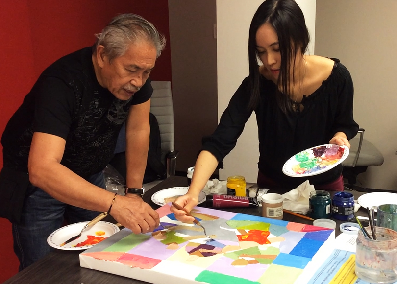 "World-renowned UNICEF artist Manuel Baldemor and artist/PMNTV host Michelle Chermaine at the Philippine Consulate General in Toronto, collaborating on an abstract painting inspired by Baldemor's recollection of the late Jose P. Alcantara's sculpture ""Hapunan."" Michelle is the grandniece of Jose P. Alcantara, who was Baldemor's friend."