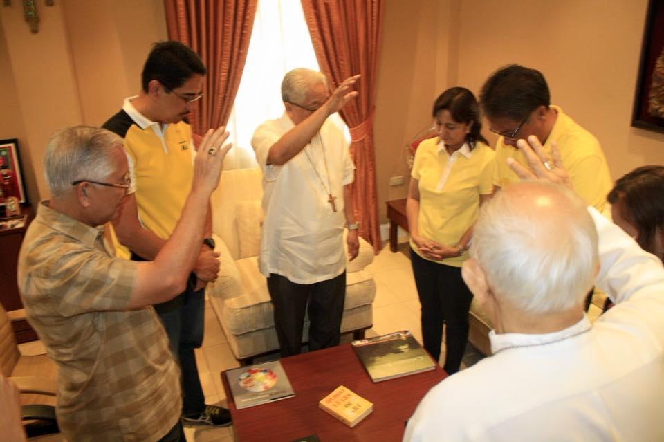 Archbishop Rolly Tirona prays over Leni Robredo and Mar Roxas at Robredo's residence on Friday.  (Photo from Robredo's Facebook page)