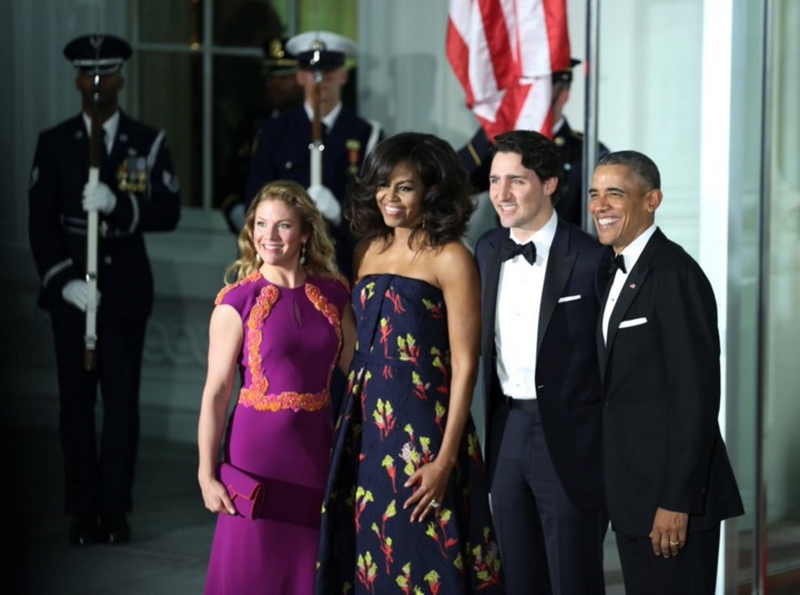 Sophie Gregoire-Trudeau (first from left) wears a bright purple dress with coral flower trim by Canadian designer Lucian Matis while First Lady Michelle Obama (second from left) dons a strapless midnight blue floral jacquard gown with asymmetrical draping created by one of her favorite designers, Jason Wu.